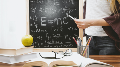 Centro foto: lavagna. Su cattedra: libri, occhiali, mela, portapenne. A destra: docente con gessetto